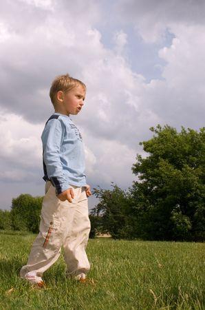 Boy staying in summer park