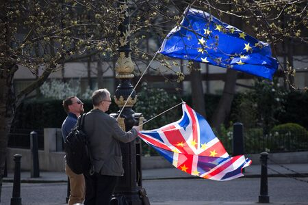London - MARCH 25: Two men wave with the EU and British flags during the Unite for Europe prostest march against Brexit. The demonstrators marched to express their positive opinion of Britain´s membership in the European Union after the country voted to l
