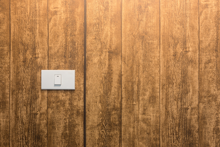 White electric switch on wooden wall
