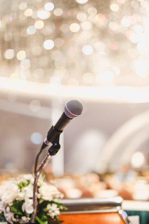 Microphone on the speech podium over the Abstract of conference hall or seminar room with attendee and bokeh, Business meeting concept. Stock Photo