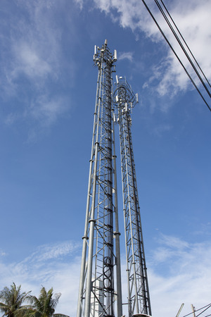 Telecommunication tower with antennas with blue sky repeater antenna, Mobile phone network antenna
