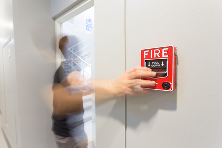 The man running and hand is pulling fire alarm on the wall next to the emergency exit door.