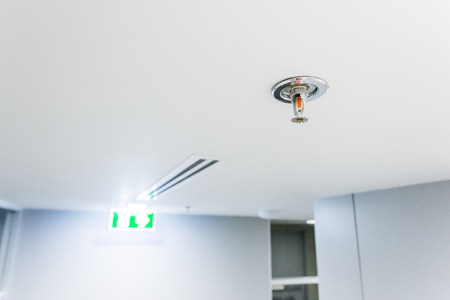 Fire Sprinkler Fireplace in the office for safety and to reduce damage in case of fire, signage exit blur background. Stock Photo