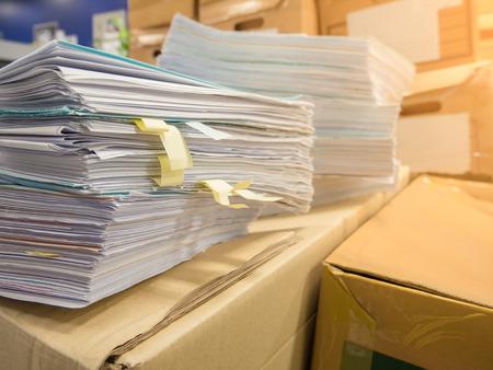 Pile di carta per documenti e cartella di file davanti a sfondo di scatole di cartone, concetto di lavoro duro, sacco di lavoro.