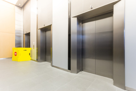 Modern steel elevator repairing  cabins in a business lobby or Hotel, Store, interior, office,perspective wide angle. Three elevators in hotel lobby.