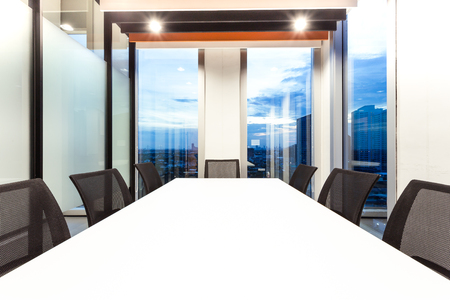 Modern meeting room with for present, large windows outside building with blue sky and clouds, twilight sky, city, tower view, soft focus Stock Photo