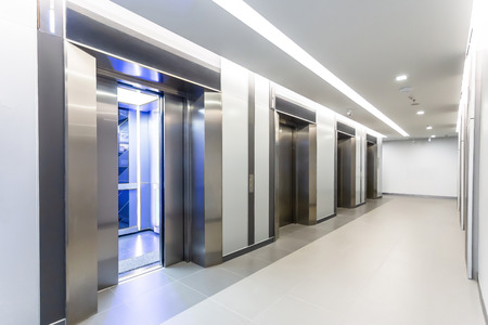 Modern steel elevator door open 50% cabins in a business lobby or Hotel, Store, interior, office,perspective wide angle. Four elevators in hotel lobby.