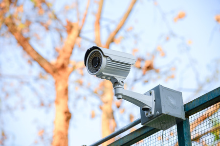 Security Camera CCTV over fence blue sky photo