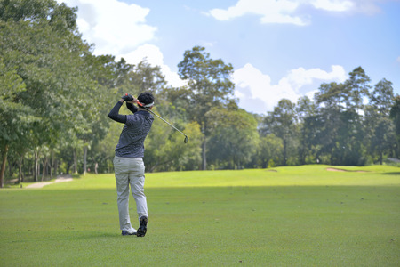 golfing: Golf player pitching the golf ball, ball in the air.