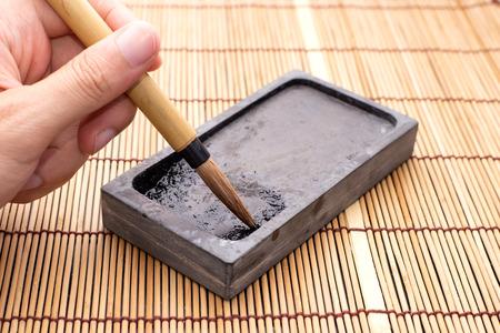 Hand holding Chinese brushes on inkstone writing instrument
