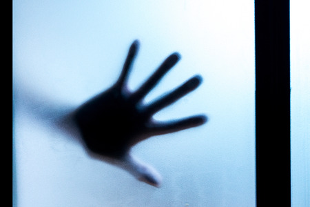 hand movements: Shadow of hands behind frosted glass in the back light. Stock Photo
