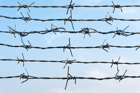 Group Rusty barbed wire against blue sky photo