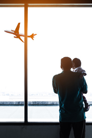 Father holding his baby in airport with airplane on background.