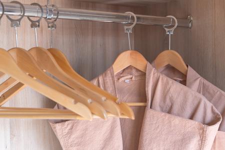 bathrobe with wooden hangers in wardrobe Standard-Bild