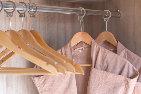 bathrobe with wooden hangers in wardrobe Stock Photo