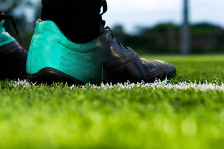 foot of a soccer or football player on green grass