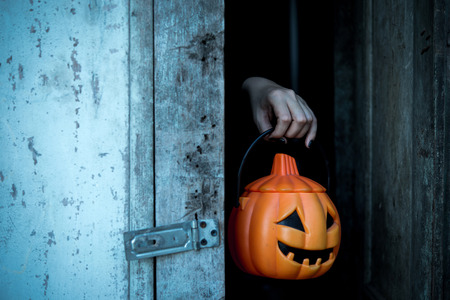 portrait young girl studio: Hands of ghost holding lantern giant pumpkin, Halloween image.