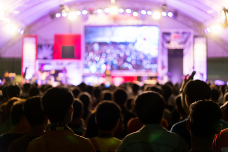 blurred image of Audience enjoying music in front of concert stage