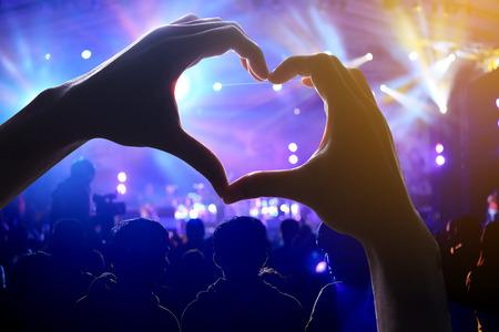 심장 모양의 손 그림자와 함께 콘서트 도중에서 관객의 군중 스톡 콘텐츠