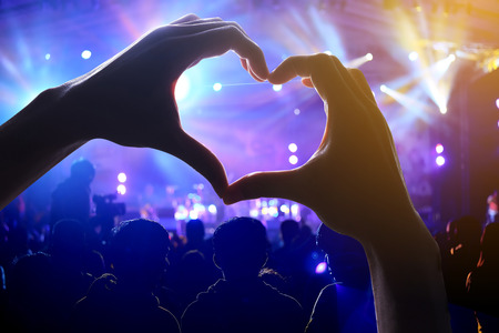 party silhouettes: Crowd of Audience at during a concert with a heart shaped hands shadow Stock Photo