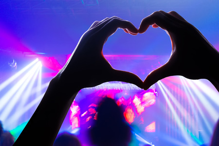 engage your audience with the power of music, with a heart shaped hands shadow Standard-Bild