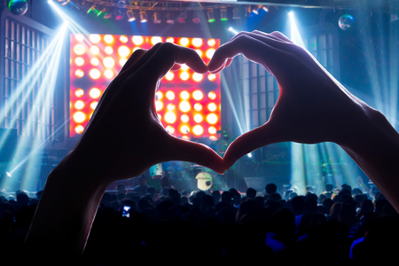 Coinvolgere il pubblico con il potere della musica, con un cuore a forma di mani ombra Archivio Fotografico - 46205670