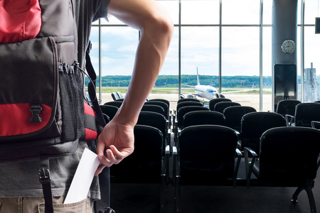 airport terminal: traveler presenting passenger tickets for flight at counter check-in airport