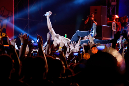 blurred image of singer on top crowd surfing at a music festival Stock Photo