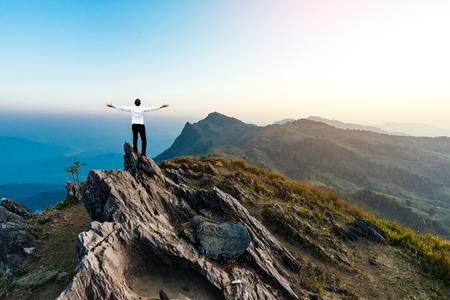 businessman success hiking on the peak of rocks mountain at sunset, success,winner, leader concept
