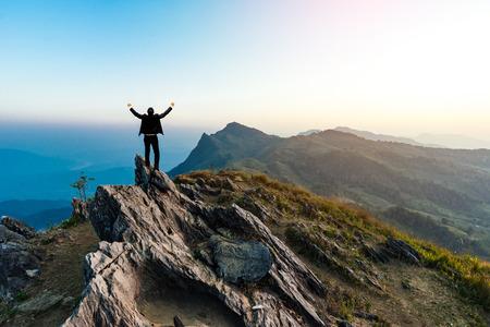 el éxito empresario de excursión en el pico de la montaña de rocas al atardecer, éxito, ganador, líder concepto Foto de archivo