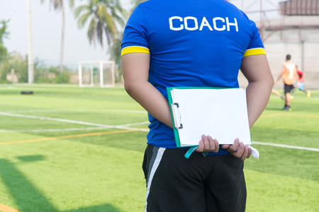 Coach is coaching Children Training In Soccer Team Stock Photo