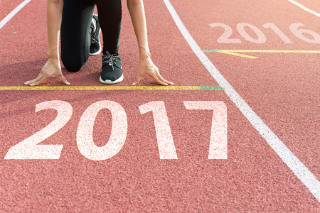 Athlete on starting line waiting for the start in running track with text 2017 year, Start to new year 2017