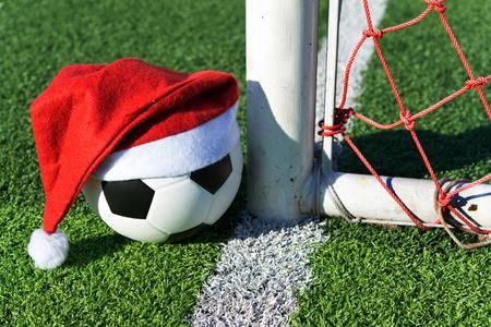 Weihnachtsmann roten Hut auf Fußball im grünen Gras Standard-Bild