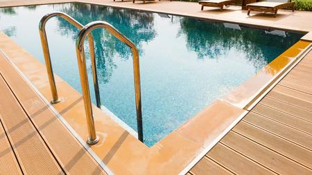 metallic stairs: Grab bars metallic ladder entrance to clear blue swimming pool Stock Photo