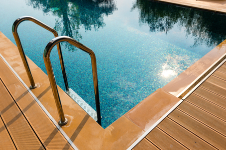 grab: Grab bars metallic ladder entrance to clear blue swimming pool Stock Photo