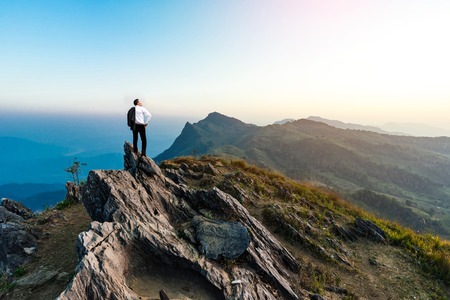 businessman success hiking on the peak of rocks mountain at sunset, success winner, leader concept