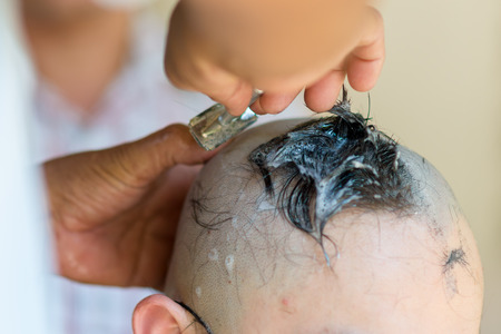 ordinate: knife cutting hair at the ordination ceremony of a Buddhist monk in thailand