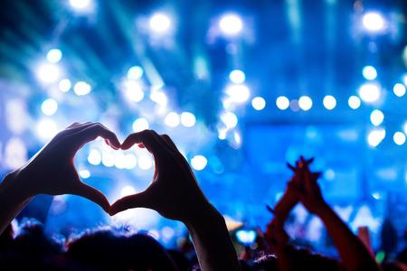 Crowd of Audience tijdens een concert met silhouet van een hartvormige handschaduw, licht verlicht is de kracht van het muziekconcert Stockfoto