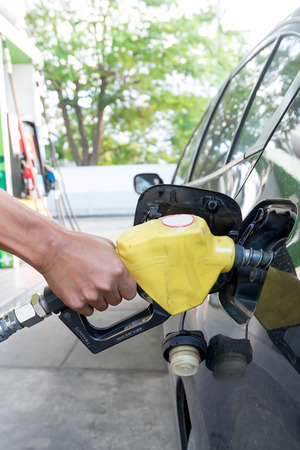 natural gas prices: Pumping gas at gas pump. Closeup of man pumping gasoline fuel in car at gas station Stock Photo