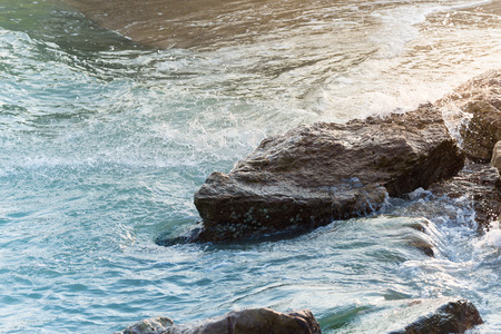 white perch: Clear sea water waves breaking on rocks with water splashes