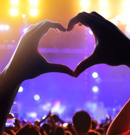 音楽コンサートの力である照らされた光のライブ コンサートでの観客の群衆の手とハートのシルエット