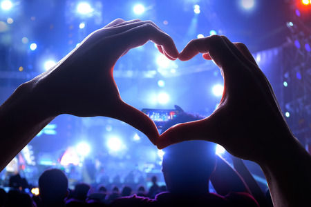 Silhouette of a heart shaped hands and crowd of Audience at live concert, light illuminated is power of music concert