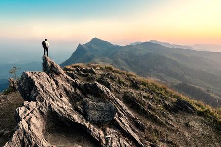 日没、成功、勝者、リーダーの概念で岩山のピークに実業家ハイキング