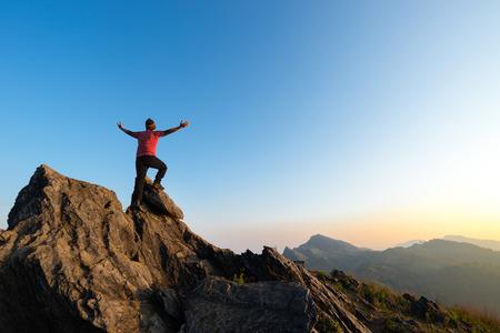 Winner on peak of rocks mountain Hike at sunset, Active life concept