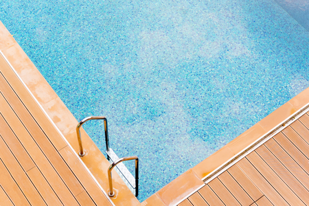 Grab bars metallic ladder entrance to clear blue swimming pool Stock Photo