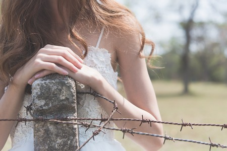 Woman in white wedding dress her hands picking a Rusty barbed wire scared and alone