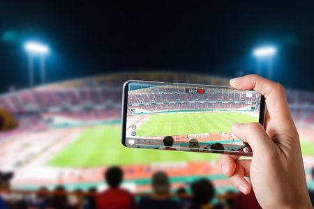 People hands use smartphones record soccer competition match in football stadium live streaming video on internet to social media comment chat to Friend