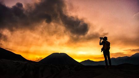 Photographer taking photos on beautiful moment mountains at Sunset Standard-Bild