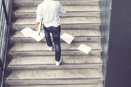 businessman hurrying time with papers document on ground