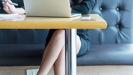 Laptop on table with businesswoman sitting at sofa in coffee shop